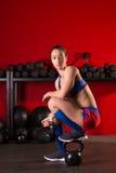La donna di Kettlebell si rilassa dopo l'allenamento in palestra rossa Fotografia Stock Libera da Diritti