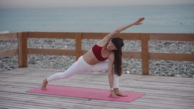 La donna di mezza età fa l'yoga sulla spiaggia archivi video