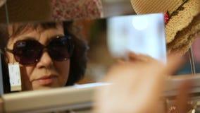 La donna di mezza età prova sopra gli occhiali da sole eleganti stock footage