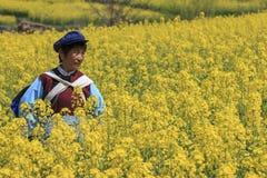 La donna di NaXi si è vestita con l'abbigliamento tradizionale di minoranza in un fiore del seme di ravizzone vicino al villaggio Fotografie Stock Libere da Diritti