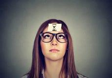 La donna di pensiero con la sabbia cronometra l'autoadesivo sulla fronte Concetto della gestione di tempo Immagini Stock