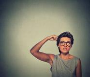 La donna di pensiero Contused con i vetri ha sconcertato il graffio della sua testa Fotografie Stock Libere da Diritti