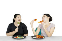 La donna di peso eccessivo che esamina l'amico mangia la pizza Fotografia Stock