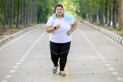 La donna di peso eccessivo che fa i funzionamenti si esercita sulla strada immagine stock