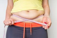 La donna di peso eccessivo con nastro adesivo sta misurando il grasso sulla pancia Immagini Stock
