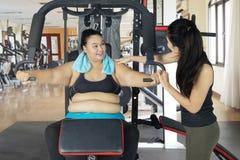 La donna di peso eccessivo esegue l'esercizio alla palestra Fotografia Stock