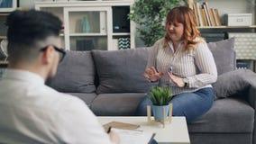 La donna di peso eccessivo turbata sta aprendosi al terapista maschio preoccupantesi in ufficio video d archivio