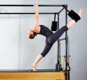 La donna di Pilates in gambe spaccate della Cadillac allunga l'esercizio Fotografie Stock