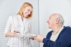 La donna di professione d'infermiera sta portando un pasto all'uomo anziano immagini stock