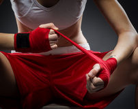 La donna di pugilato lega la fasciatura sulla sua mano, prima della formazione Immagini Stock