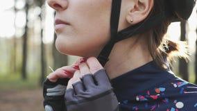 La donna di riciclaggio messa a fuoco mette sul cablaggio delle clip e del casco prima della corsa di triathlon Concetto di triat stock footage