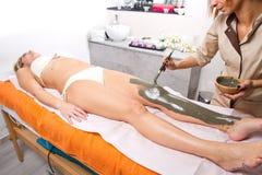 La donna di rilassamento che si trova su un massaggio presenta la ricezione dei treatmen di un fango Immagine Stock