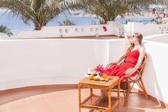 La donna di riposo sta sedendosi e dreamingin una sedia al terrazzo. Fotografia Stock