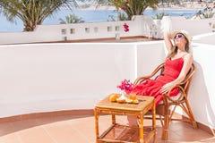 La donna di riposo sta sedendosi e dreamingin una sedia al terrazzo. Fotografia Stock Libera da Diritti