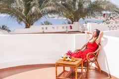 La donna di riposo sta sedendosi e dreamingin una sedia al terrazzo Fotografia Stock