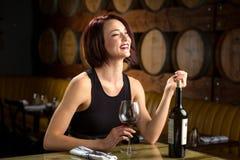La donna di risata della datazione di divertimento data il bicchiere di vino di notte alla cantina con i barilotti nel fondo Fotografia Stock Libera da Diritti