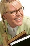 La donna di risata trasporta la pila di libri Immagine Stock Libera da Diritti