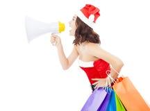 La donna di Santa di Natale che per mezzo di un megafono con il regalo insacca Immagini Stock Libere da Diritti