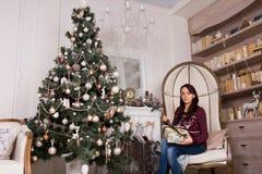 La donna di seduta con i presente si avvicina all'albero di Natale immagini stock