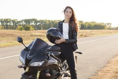 La donna di sguardo piacevole ha giro del motociclista, posa sulla bici fresca, tiene il casco, porta il bomber, gradisce lo spor fotografia stock libera da diritti