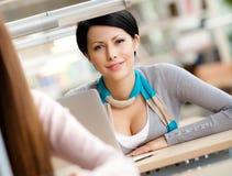 La donna di smiley si siede alla tabella Fotografia Stock Libera da Diritti