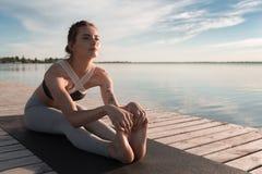 La donna di sport dei giovani alla spiaggia fa l'allungamento degli esercizi Fotografia Stock
