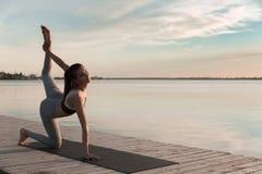 La donna di sport dei giovani alla spiaggia fa l'allungamento degli esercizi Fotografia Stock Libera da Diritti