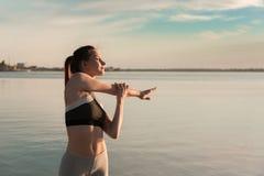 La donna di sport dei giovani alla spiaggia fa l'allungamento degli esercizi Immagini Stock Libere da Diritti
