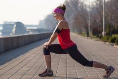 La donna di sport ha allungamento dell'addestramento fuori nella mattina Fotografia Stock