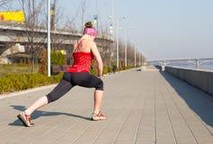 La donna di sport ha allungamento dell'addestramento fuori nella mattina Fotografia Stock Libera da Diritti