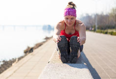 La donna di sport ha allungamento dell'addestramento fuori nella mattina Immagini Stock