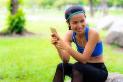 La donna di sport listten alla musica sul telefono cellulare che esamina fotografia stock