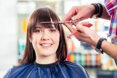 La donna di taglio del parrucchiere batte i capelli in negozio Immagine Stock Libera da Diritti