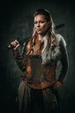La donna di Viking con l'arma fredda in un guerriero tradizionale copre fotografia stock libera da diritti
