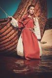 La donna di Viking in vestiti tradizionali si avvicina a drakkar immagine stock libera da diritti