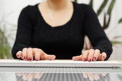 La donna di vista frontale sta scrivendo sulla tastiera bianca a casa fotografia stock