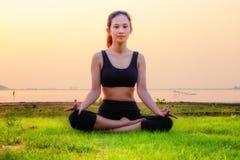 La donna di yoga è si rilassa con il bello fondo del tramonto sul Fotografia Stock