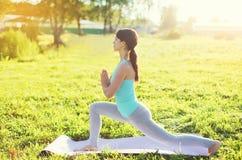 La donna di yoga che fa l'allungamento si esercita su erba di estate Fotografie Stock Libere da Diritti