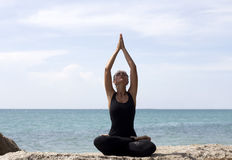 La donna di yoga posa sulla spiaggia vicino al mare ed alle rocce Fotografia Stock Libera da Diritti