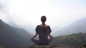 La donna di yoga si siede nella posa di meditazione sulla scogliera della montagna in Sapa, Vietnam stock footage