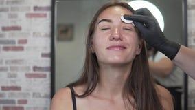 La donna dipinge le sopracciglia in un salone di bellezza archivi video