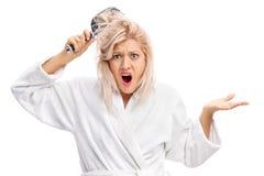 La donna dispiaciuta con i suoi capelli ha aggrovigliato in una spazzola per i capelli Fotografia Stock Libera da Diritti