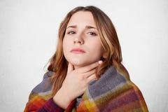 La donna dispiaciuta coperta di coperta calda, ha gola del thore, può ` t dire tutta la parola, sguardi con l'espressione malata  fotografie stock