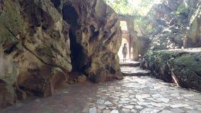 La donna distante entra nella caverna attraverso l'arco di pietra contro luce archivi video