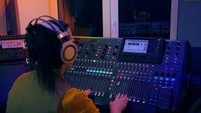 La donna DJ lavora alla console mescolantesi a colori l'illuminazione archivi video