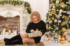 La donna dolce sorride e posa la seduta sul fondo del Natale immagine stock