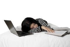 La donna dorme sul letto con il computer portatile ed i libri Fotografie Stock