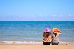 La donna due si siede sulla spiaggia Fotografia Stock Libera da Diritti