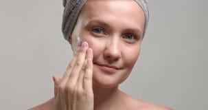 La donna durante il trattamento facciale mette una crema su una guancia e massaggia un fronte video d archivio