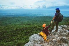 La donna e gli uomini che dell'amante gli asiatici viaggiano si rilassano nella festa La mappa di vista esplora le montagne fotografie stock libere da diritti